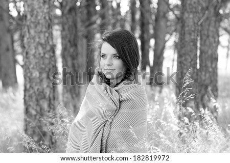 Woman Wrapped In Blanket - This is a black and white photo of a cute young woman wrapped in a warm blanket on a cool fall day. Shot with a shallow depth of field.