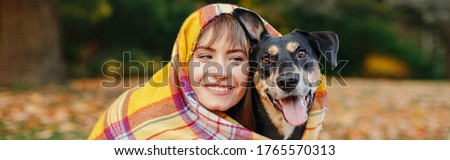 Woman wrapped in woollen blanket with dog in autumn fall park. Caucasian woman sitting on ground hugging domestic animal pet. Best friends forever. Web banner header for website.