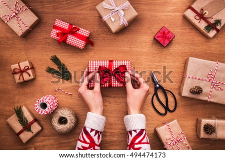 Woman wrapping modern christmas gifts. Close up on hands tying perfect bow. Wrapping inspiration. Christmas presents on a wooden table.
