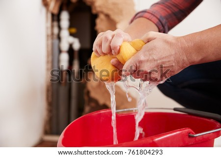 Woman wringing water out of a sponge into a bucket, detail