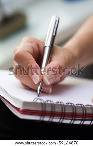 Woman writes on a paper