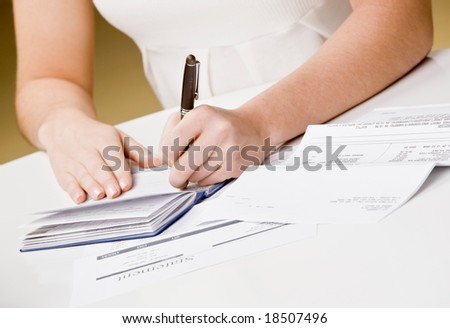 Woman writing checks from checkbook to pay monthly bills