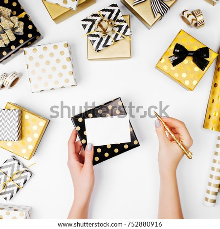 Woman writing Greeting Card for Christmas presents. Christmas decoration background in golden and black colors. Flat lay, top view