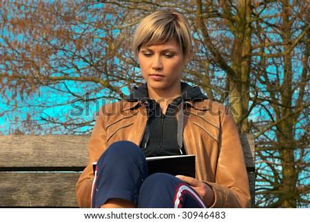 Woman writing on a bench in a park.
