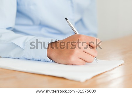 Woman writing on a sheet of paper while sitting at the office