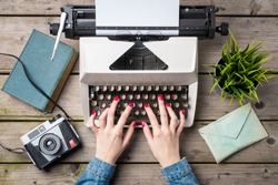 Woman writing on an old typewriter