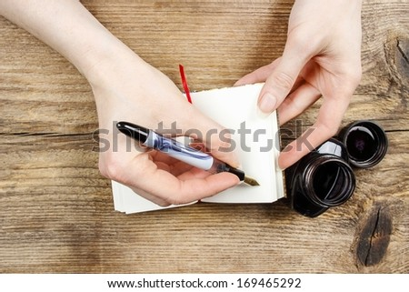 Woman writing on notebook. Wooden background