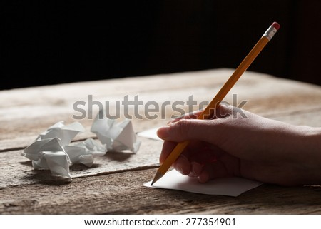 woman writing on sheet of paper
