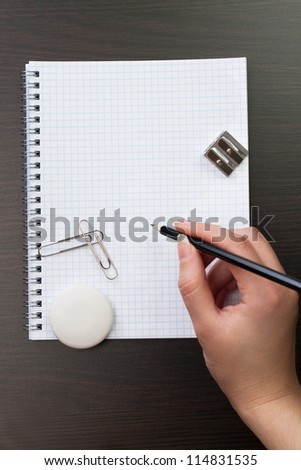 woman writing with pencil on notebook in office