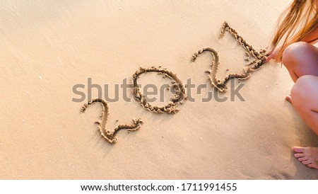 woman writting 2021 on sand beach. ocean wave and lettering on the beach. Happy New Year 2021. tropical vacation 2021.