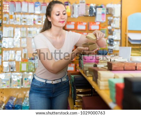 Woman 30-35 years old is choosing small boxes for gifts in store.