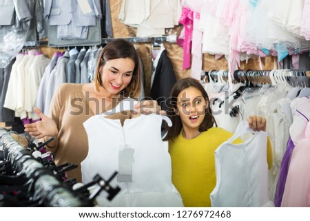 Woman 25-29 years old with girl 10-15 years old are acquiring fashionable dress in children's clothing store.
