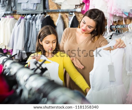 Woman 25-29 years old with girl 10-15 years old are shopping in dresses store.
