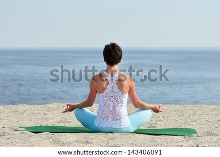 Woman yoga on the beach