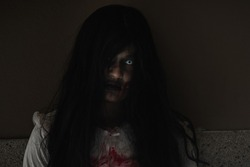 Woman zombie in blood. Closeup face and eyes of Asian Woman ghost with blood. Horror creepy scary fear in a dark house. Hair covering the face, Halloween festival concept