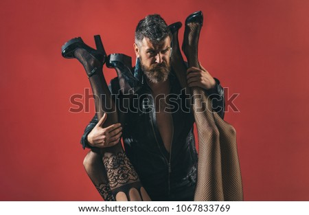 Womanizer. Bearded brutal man with female legs in sexy pantyhose. Seductive sensual relationship. Passion and polygamy. Fashion and beauty. Pimp and model agent. Man and two women, seductive legs