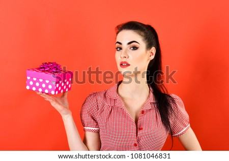 Womans day, Christmas, shopping, New Year, Black Friday concept. Lady with gift isolated on red background. Girl with serious face, make up and pink pack. Woman in stylish dress holds present. #1081046831