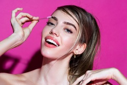 Womans eyebrows. Beauty. Beautiful girl with eyebrow brush on pink background. Girl with natural make up. Eyebrow correction