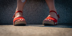 Womans feet in red shoes closeup with green footnails