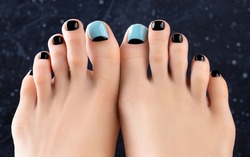 Womans feet on dark background. Beautiful spring summer blue and black nail design. Manicure, pedicure beauty salon concept.