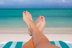 Womans feet on the beach