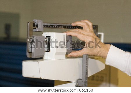 womans hand adjusts the scale