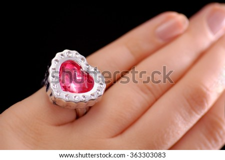 Stock photo of a woman's hand, close up, with neutral manicure and large sparkly pink heart ring.
