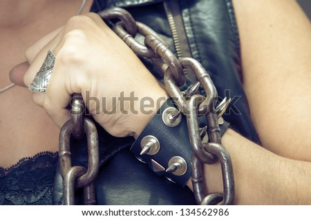 Womans hand holding a chain, with leather bracelet