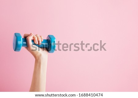 Womans hand holding blue dumbbell isolated on pink background. Equipment for home workout. Fitness and activity. Sport and healthy lifestyle concept. Copy space in right side Stock photo ©