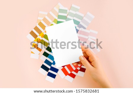 Womans hand holding empty card. Mockup with fashion colour swatches. Color trend palette.