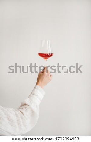 Womans hand holding glass of rose wine over white wall background. Wine shop, wine tasting, bar, wine list concept