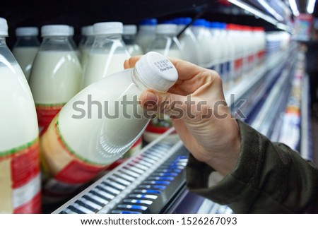 Womans hand holding milk bottle in supermarket. Man shopping milk in grocery store. Man checks product expiration date before buying it. Close-up.