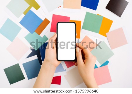 Womans hand holding smartphone with blank screen. Smartphone mockup with fashion colour swatches. Color trend palette.