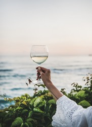 Womans hand in white lace dress sleeve holding glass of white wine with beautiful sunset colors and sea horizon at background. Summer picnic and refreshment drink concept