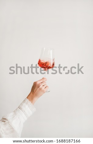 Womans hand in white shirt holding and turning glass of rose wine over white wall background. Wine shop, wine tasting, bar, wine list concept