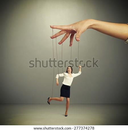 womans hand manipulating puppet over dark background