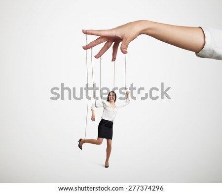 womans hand manipulating the small puppet over light grey background