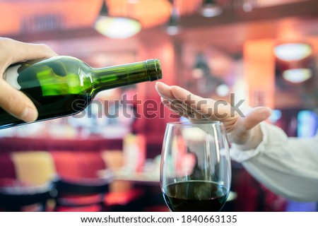 Womans hand rejecting more alcohol from wine bottle in bar concept for alcoholism or drunk driving Foto stock ©