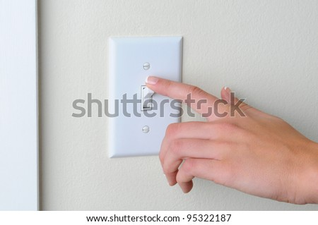 Womans hand with finger on light switch, about to turn off the lights. Closeup of hand and switch only. Horizontal format. Foto d'archivio ©