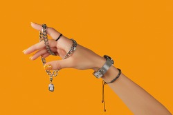 Womans hand with jewelry accessories over orange background