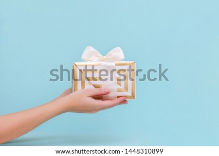 Womans hands holding gift or present box on blue pastel background.