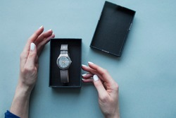 Womans hands opens black gift box with grey watchs. Flat lay. Top view. Space for text. Grey background. Luxury gift