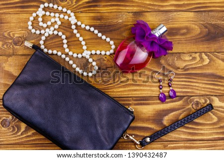77d358b3 Women accessories on wooden background. Clutch bag, bottle of perfume,  pearl necklace and