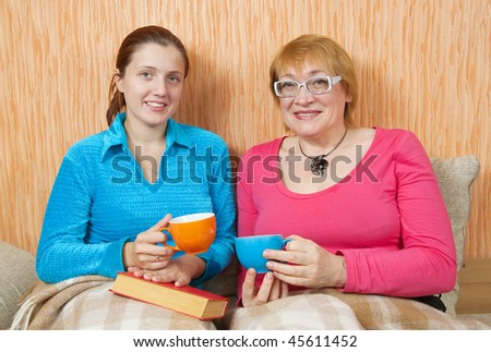 women and her adult daughter having tea  on sofa at home - stock photo