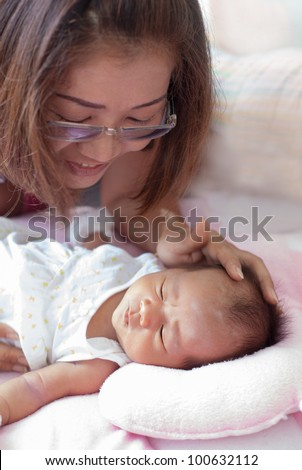 women and infant asleep on the baby bed