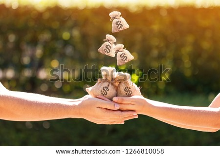 Women and man hands hold a money bags and dropping on the top in the public park for loans to planned investment is together in the future concept.