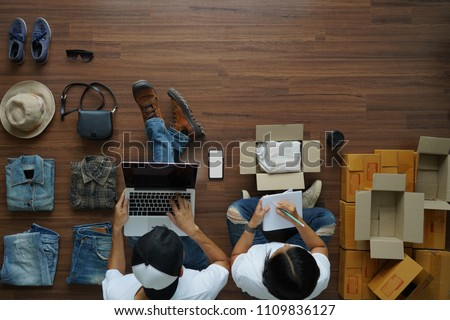 Women and men selling online start up small business owner working with using laptop computer and write a notebook on wooden floor with fashion clothes accessories and postal parcel in her home