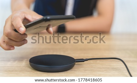 Women are charging smartphones with a wireless charging dock or wireless charging pad. She's picking up a smartphone from a wireless charging dock on wooden table in wireless technology concept