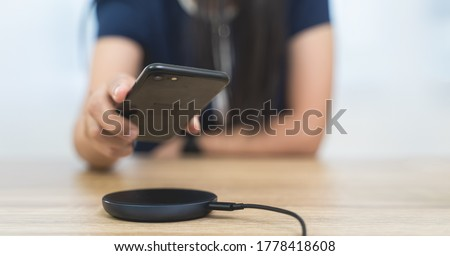 Women are charging smartphones with a wireless charging dock or wireless charging pad. She's picking up a smartphone from a wireless charging dock on wooden table in wireless technology concept Photo stock ©