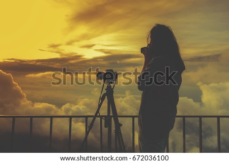 Women are happy to take photo at the mountains with fog. Women are photographer, have fair lighting or over sunlight.